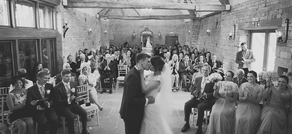 Guests smile and clap as the newlyweds kiss after saying their wedding vows – wedding ceremony