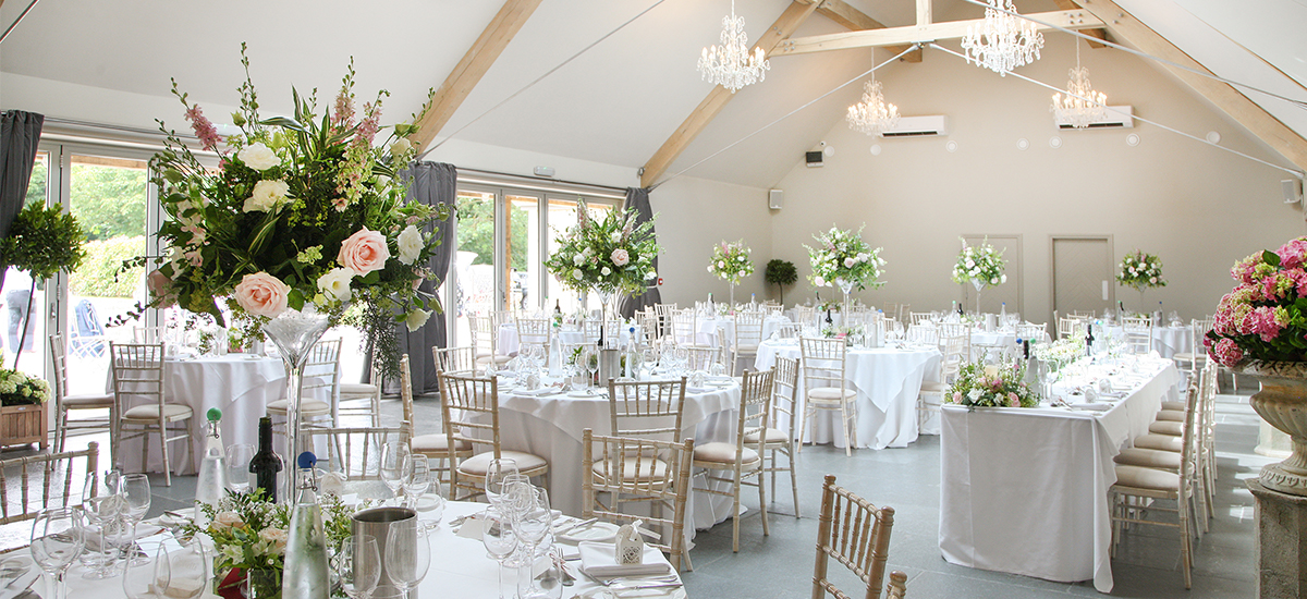 The Orchard Barn at Blackwell Grange is set up for an elegant wedding reception with tall pink and ivory floral table centrepieces