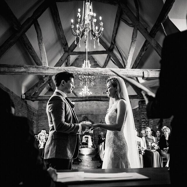 A bride and groom hold hands in the beautiful Thatch Barn as they say their wedding vows Photographer